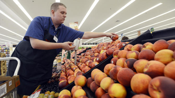 FILE-In this Monday, Aug 27, 2012, file photo, Caleb Tollefson stocks a display of nectarines and peaches at a Hy-Vee grocery store in Sioux Falls, S.D.  (AP Photo/Argus Leader, Elisha Page)