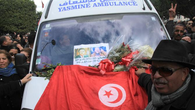 Protesters gather with a Tunisian flag at the ambulance carrying the body of opposition leader Chokri Belaid in Tunis, Wednesday, Feb. 6, 2013. The Tunisian opposition leader critical of the Islamist-led government and violence by radical Muslims was shot to death Wednesday,  the first political assassination in post-revolutionary Tunisia. The killing is likely to heighten tensions in the North African nation whose path from dictatorship to democracy so far has been seen as a model for the Arab world. (AP Photo/Amine Landoulsi)