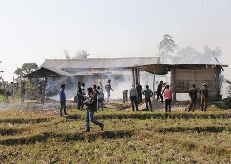 Tribal plantation workers burn houses belonging to indigenous Bodo tribesmen after ethnic clashes in Balijuri village