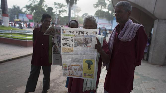 Indian porters or luggage carriers read a newspaper with front-page news of Nepal earthquake outside a railway station in Gauhati, India, Sunday, April 26, 2015. A strong magnitude-7.9 earthquake shook Nepal's capital and the densely populated Kathmandu Valley before noon Saturday, causing extensive damage with toppled walls and collapsed buildings, officials said. (AP Photo/Anupam Nath)
