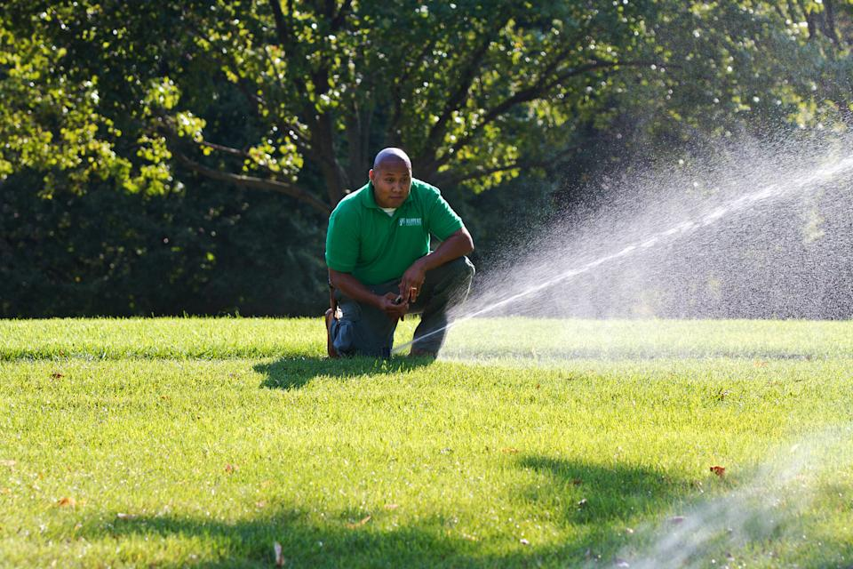 In this 2012 publicity photo provided by PLANET, a landscape professional checks for water distribution uniformity and makes sure the irrigation systems are installed and maintained properly. (AP Photo/PLANET, National Landscape Industry Association, Philippe Nobile)
