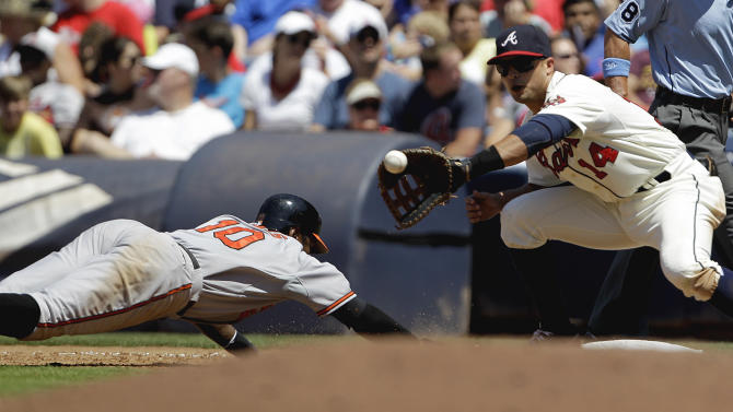 Baltimore Orioles' Adam Jones, left, dives back to first base to beat the throw to Atlanta Braves' Martin Prado, right, from pitcher Randall Delgado in the sixth inning of a baseball game on Sunday, June 17, 2012, in Atlanta. (AP Photo/David Goldman)