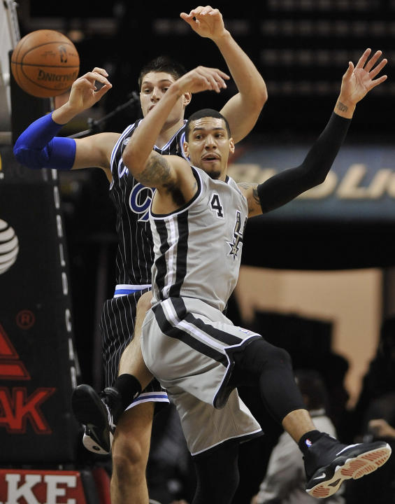 San Antonio Spurs guard Danny Green, front, and Orlando Magic center Nikola Vucevic, chase a loose ball during the first half of an NBA basketball game on Saturday, March 8, 2014, in San Antonio. San