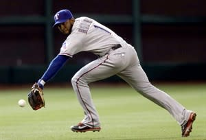 Texas Rangers shortstop Elvis Andrus reaches low for the ball on Houston Astros' Justin Maxwell's single in the seventh inning of a baseball game, Wednesday, April 3, 2013, in Houston. The Rangers won 4-0. (AP Photo/Pat Sullivan)