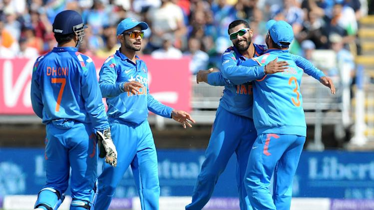 India's Ravindra Jadeja, 2nd right, is congratulated by Suresh Raina, right, after bowling England's Eoin Morgan caught Suresh Raina for 32 runs during the fourth One Day International match between England and India at Edgbaston cricket ground, Birmingham, England, Tuesday, Sept 2, 2014. (AP Photo/Rui Vieira)