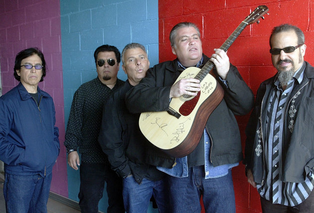 FILE - This April 7, 2004 file photo shows members of the band Los Lobos, from left, Louie Perez, Cesar Rosas, Conrad Lozano, David Hidalgo holding a guitar, and Steve Berlin posing for a photograph, in Los Angeles. They are the progenitors of Chicano rock 'n' roll, the first band that had the boldness, and some might say the naiveté, to fuse punk rock with Mexican folk tunes. (AP Photo/Damian Dovarganes, file)