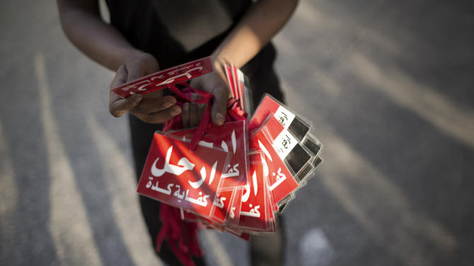 """An Egyptian street vendor holds red cards reading in Arabic,""""leave - enough already, as a message to President Mohammed Morsi, near the Ministry of Culture in Cairo, Egypt, Wednesday, June 26, 2013. In abstract terms, protests planned for Sunday aiming to force out Egypt's Islamist president violate a basic principle of democracy: If an election has been held, all must respect the results, otherwise it's political chaos. Supporters of President Mohammed Morsi have been angrily making that argument for days. Those behind the protests insist he lost the legitimacy of that election victory by power grabs and missteps. (AP Photo/Manu Brabo)"""