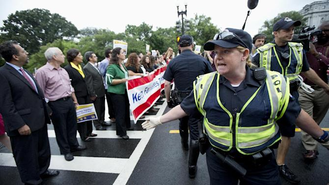 FILE - This Aug. 1, 2013 file photo shows Capitol Hill Police officers trying to clear a street on Capitol Hill in Washington that was blocked by immigration reform supporters during a rally protesting immigration policies and the House GOP's inability to pass a bill that contains a pathway to citizenship. During Congress' last attempt to remake the immigration system, in 2007, a public backlash helped kill the bill as angry calls overwhelmed the Senate switchboard. This summer other issues, notably President Barack Obama's health care law, seem to be topping the list of voters' concerns. Constituents opposed to citizenship for immigrants in this country illegally are loudly voicing their views at Republican House members' town hall meetings this month. But advocates of immigration legislation with a path to citizenship are having some success getting their supporters to show up, too, even in heavily Republican districts. (AP Photo/Manuel Balce Ceneta, File)