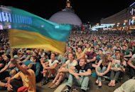 Ukrainian supporters cheer on their team as they watch Ukraine play Sweden in a Group D match at the Euro 2012 football championships on a giant screen in the fan zone in Kiev on June 11, 2012. Thousands of supporters gathered in Kiev to watch the match.  AFP PHOTO /GENYA SAVILOV