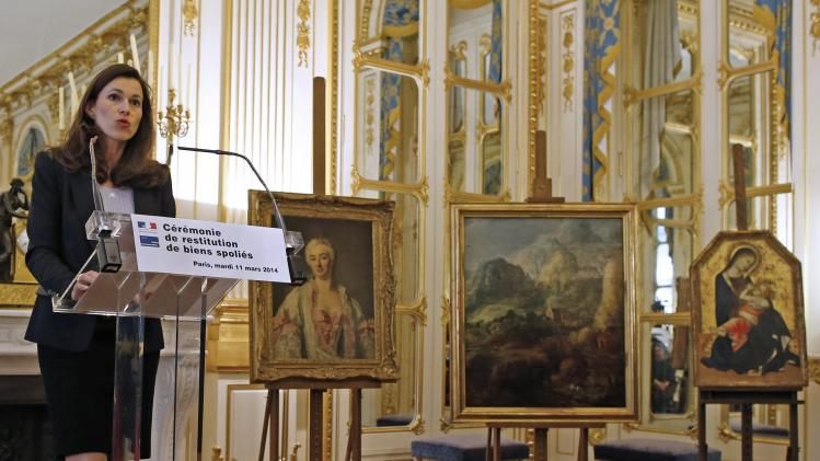 French Culture Minister Filippetti speaks on a podium near three paintings seized by the Nazis at an official ceremony at the ministry to announce their return to their rightful owners, in Paris