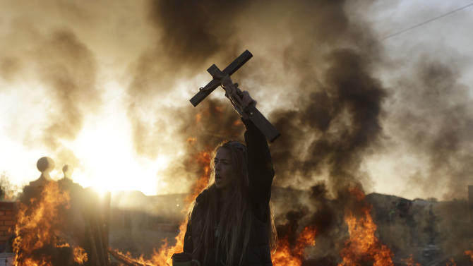 An Irish traveler resident holds up a cross for the media, in front of a burning barricade during evictions at the Dale Farm travellers site, near Basildon England, 30 miles (50 kilometers) east of London, Wednesday, Oct. 19, 2011.  Police in riot gear used sledgehammers to clear the way for the eviction of a community of Irish Travellers from a site where they have lived illegally for a decade.  A large force of police and bailiffs faced resistance from several dozen residents and supporters who threw bricks and struggled with officers.  (AP Photo/Matt Dunham)