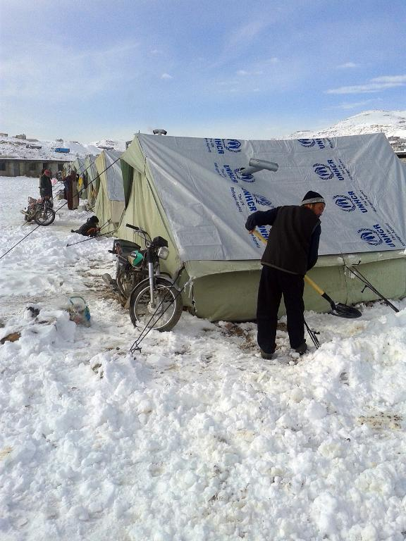 A Syrian refugee shovels snow following a storm in the town of Arsal in the Lebanese Bekaa valley on December 12, 2013