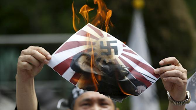An anti-Japan activist burns a poster depicting Japanese Prime Minister Shinzo Abe with a swastika on a rising-sun flag during an anti-Japan rally in front of the Japanese embassy in Seoul