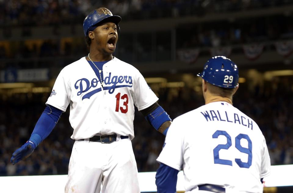 Los Angeles Dodgers' Hanley Ramirez (13) reacts as third base coach Tim Wallach (29) watches, after Ramirez hit an RBI triple against the Atlanta Braves during the fourth inning in Game 3 of the National League division baseball series Sunday, Oct. 6, 2013, in Los Angeles. (AP Photo/Danny Moloshok)