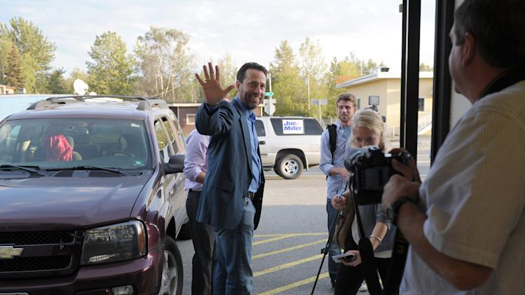 Joe Miller, center, a candidate for the Republican nomination to the U.S. Senate, waves to supporters in his Anchorage, Alaska, headquarters following the close of polling Tuesday, Aug. 19, 2014. (AP Photo/Michael Dinneen)