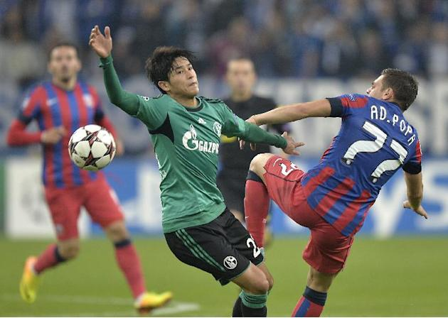 Schalke's Atsuto Uchida, left, challenges for the ball with Bucharest's Adrian Popa, right, during the Champions League Group E soccer match between FC Schalke 04 and Steaua Bucharest  in Gelsenkirche
