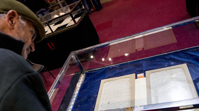 A visitor looks at Napoleon's will displayed at an auction house in Paris, France, Tuesday, Nov. 5, 2013. On Wednesday, the only known copy of this testament is being sold by Paris' Drouot Auction house. The original is in France's national archives. The copy, written by a close adviser, is expected to fetch 120,000 euros ($162,000). The 51-year-old Napoleon died in 1821 in exile on Saint Helena island, 19 days after penning the will. (AP Photo/Benjamin Girette).