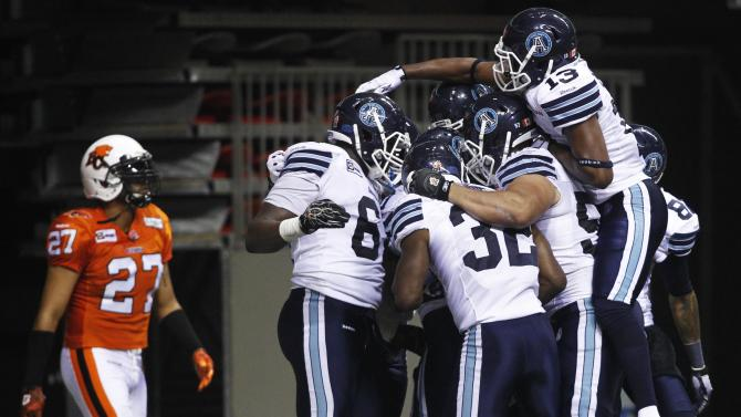 Toronto Argonauts LaVon Brazill leaps into his teammates celebrating Steve Slaton's touchdown against the B.C Lions during the second half of their CFL football game in Vancouver