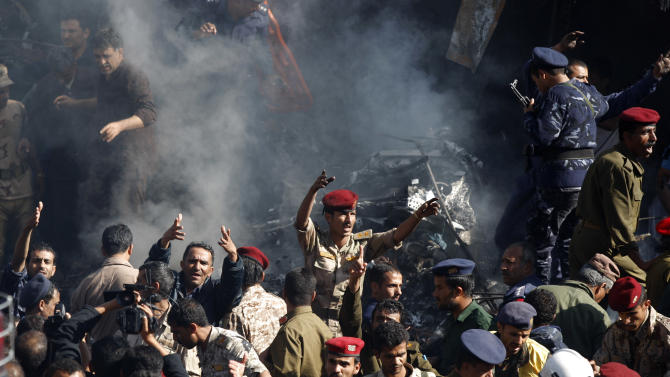 Army and police officers inspect at the scene of a plane crash in Sanaa, Yemen, Wednesday, Nov. 21, 2012. Yemeni security officials say a military plane has crashed during training over the capital, Sanaa, killing all 10 people on board. (AP Photo/Hani Mohammed)