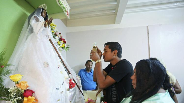 Devotees pray and make offerings to the statue of La Divina Pastora, an image of the Virgin Mary venerated by Hindus and Catholics, at the Siparia Roman Catholic Church on Good Friday in Siparia