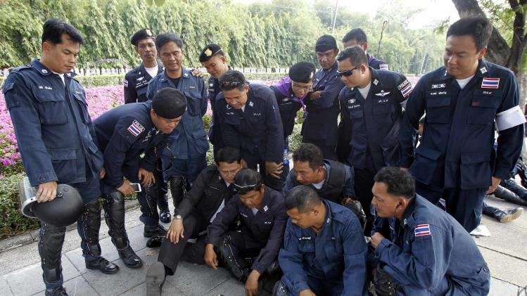 Thai riot policemen watch a television broadcast on a mobile phone at the Government House in Bangkok
