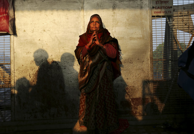 An Indian woman stands on a platform near where a stampede took place a night before, at the station in Allahabad, India, Monday, Feb. 11, 2013. The death toll from the stampede rose to 36 on Monday i