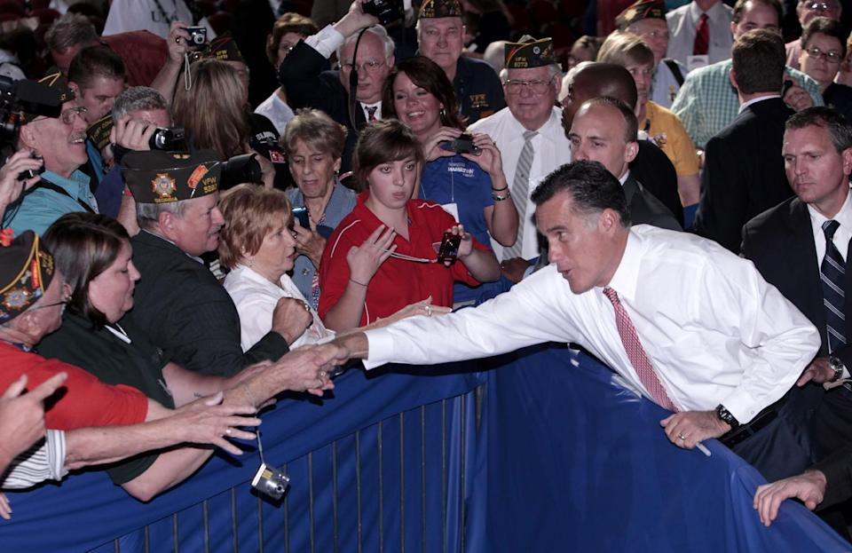 Republican presidential candidate, former Massachusetts Gov. Mitt Romney leans over a barrier to shake hands with members of the Veterans of Foreign Wars after his speech at the VFW national convention in Reno, Nev. Tuesday July 24, 2012.(AP Photo/Rich Pedroncelli)