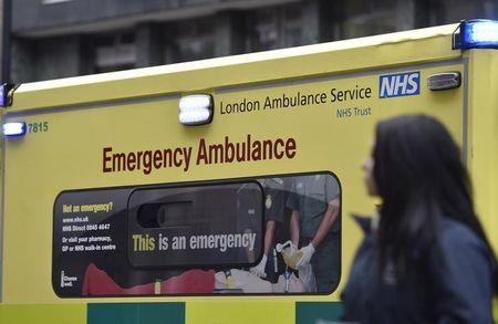 A woman passes a  National Health Service ambulance in central London
