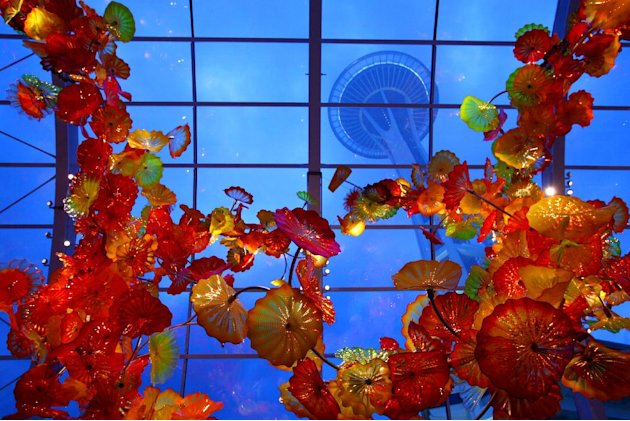 In this May 16, 2012 photo, the Space Needle towers over the Glasshouse at the new Dale Chihuly Garden and Glass museum at the Seattle Center. Fifty years after the World's Fair inserted the Space Nee