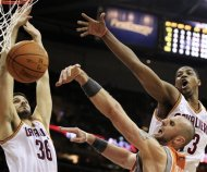 Phoenix Suns' Marcin Gortat, second from right, of Poland, loses control of the ball against Cleveland Cavaliers' Omri Casspi, left, of Israel, and Tristan Thompson, right, during the first quarter in an NBA basketball game, Sunday, March 25, 2012, in Cleveland. (AP Photo/Tony Dejak)
