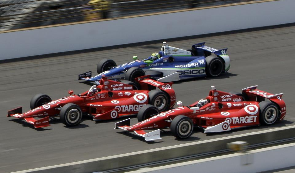 Dario Franchitti, center, of Scotland, leads teammate Scott Dixon, bottom, of New Zealand, and Tony Kanaan, top, of Brazil, to the finish line on the final lap of IndyCar's Indianapolis 500 auto race at Indianapolis Motor Speedway in Indianapolis, Sunday, May 27, 2012. (AP Photo/Dave Parker)