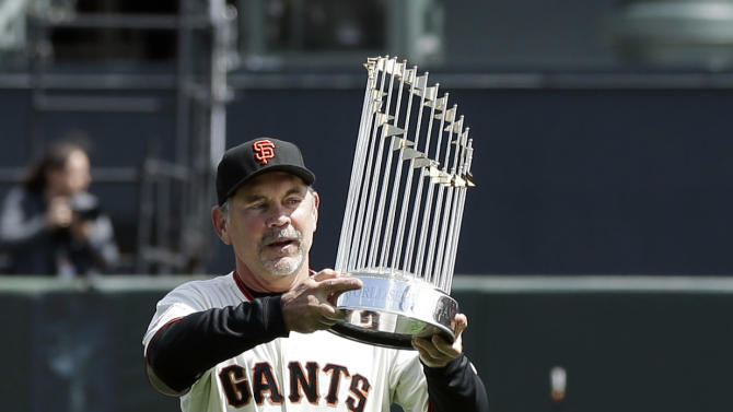 San Francisco Giants manager Bruce Bochy enters the field with the team's 2012 World Championship trophy during player introductions before a baseball game against the St. Louis Cardinals, Friday, April 5, 2013, in San Francisco. (AP Photo/Marcio Jose Sanchez, Pool)
