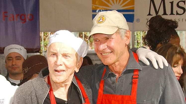 Actor Kirk Douglas and actor Harrison Ford participate in servin