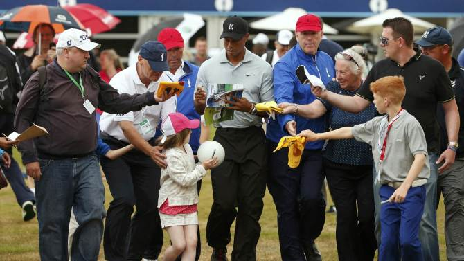 Tiger Woods of the U.S. signs autographs for fans after a practice round ahead of the British Open Championship at the Royal Liverpool Golf Club in Hoylake