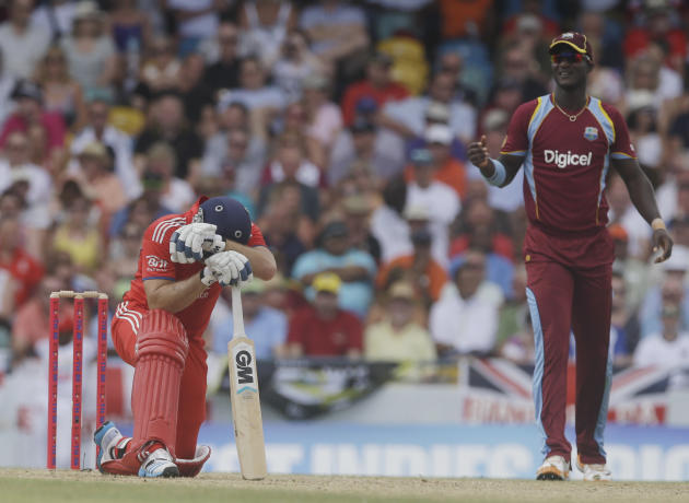 England's Michael Lumb kneels next to West Indies' Darren Sammy during their third T20 International cricket match at the Kensington Oval in Bridgetown, Barbados, Thursday, March 13, 2014. (AP