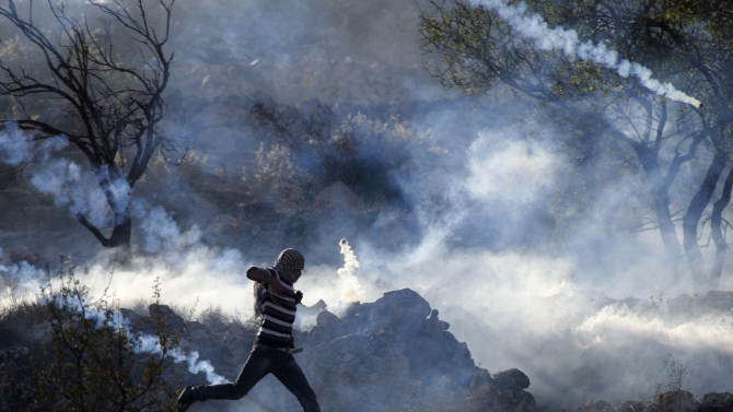 A Palestinian demonstrator runs through a cloud of tear gas during clashes against Israel's operations in Gaza Strip, outside Ofer, an Israeli military prison near the West Bank city of Ramallah, Thursday, Nov. 15, 2012. Meanwhile, Palestinian President Mahmoud Abbas cut short a trip to Europe to deal with the crisis. (AP Photo/Majdi Mohammed)