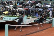 Grounds staff cover the court as rain stops the men&#39;s singles final match between Nadal of Spain and Djokovic of Serbia during the French Open tennis tournament at the Roland Garros stadium in Paris