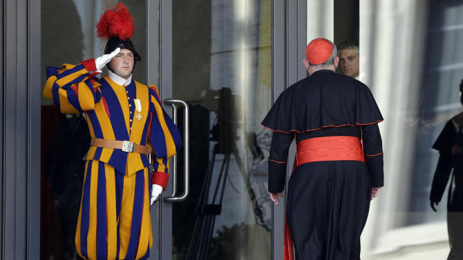 Vatican Swiss guards salute as a cardinal arrives for a meeting, at the Vatican, Monday, March 4, 2013. Cardinals from around the world have gathered inside the Vatican for their first round of meetings before the conclave to elect the next pope, amid scandals inside and out of the Vatican and the continued reverberations of Benedict XVI's decision to retire. (AP Photo/Andrew Medichini)