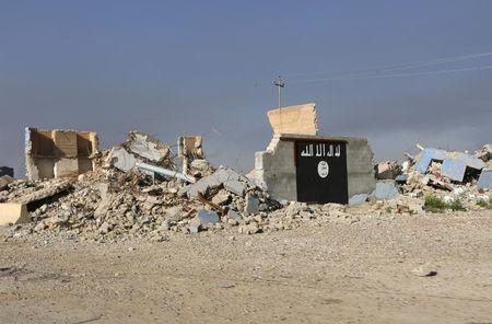 A destroyed building with a wall painted with the black flag commonly used by Islamic State militants, is seen in the town of al-Alam