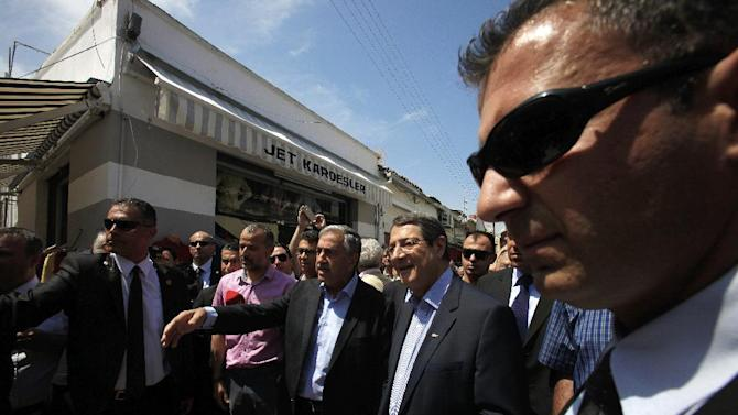 Cyprus President Nicos Anastasiades, center right, and Turkish Cypriot leader Mustafa Akinci, center, walk at a main shopping street at the breakaway northern part of the Cypriot divided capital Nicosia on Saturday, May 23, 2015. Cyprus' rival Greek and Turkish Cypriot leaders took a stroll together on both sides of the divided capital's medieval center to raise the feel-good factor, as talks aimed at reunifying the ethnically split island kick into gear. It's the first time that the leaders have done so together since the east Mediterranean island was split in 1974 when Turkey invaded after coup by supporters of union with Greece. (AP Photo/Petros Karadjias)