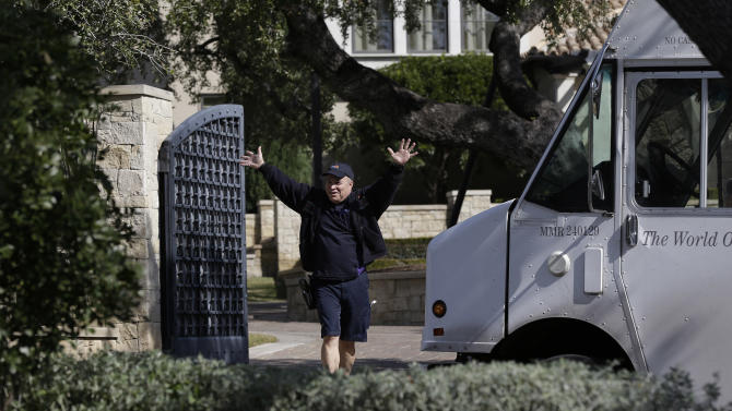 "A delivery man waves to media after dropping a package at the home of cyclist Lance Armstrong, Monday, Jan. 14, 2013, in Austin, Texas. Armstrong is scheduled to give a ""no-holds barred"" interview to Oprah Winfrey. (AP Photo/Eric Gay)"