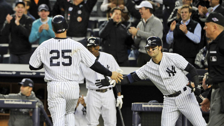 New York Yankees' Mark Teixeira (25) is greeted by teammate Nick Swisher, right, after scoring on a hit by Raul Ibanez during the fifth inning of Game 5 of the American League division baseball series against the Baltimore Orioles, Friday, Oct. 12, 2012, in New York. (AP Photo/Bill Kostroun)