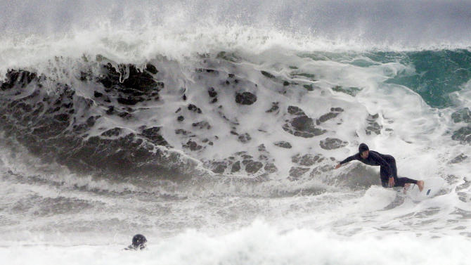 A surfer rides a wave at Blacks Beach, Tuesday, Dec. 16, 2014, in San Diego. A new storm dumped more rain on already waterlogged parts California Tuesday, bringing large surf with it to Southern California.  (AP Photo/Gregory Bull)