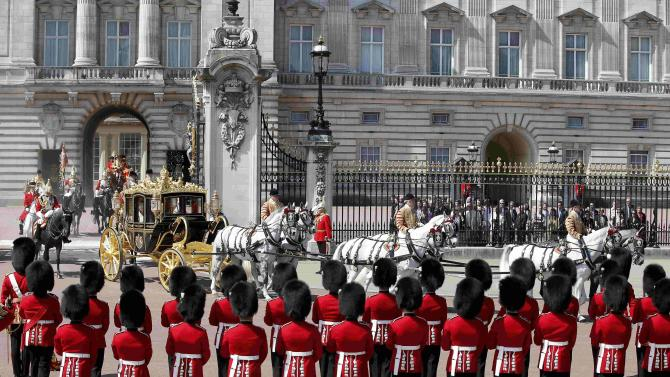 Guardsmen stand to attention as Britain's Queen Elizabeth is driven by carriage from Buckingham Palace to the Houses of Parliament during the State Opening of Parliament in central London