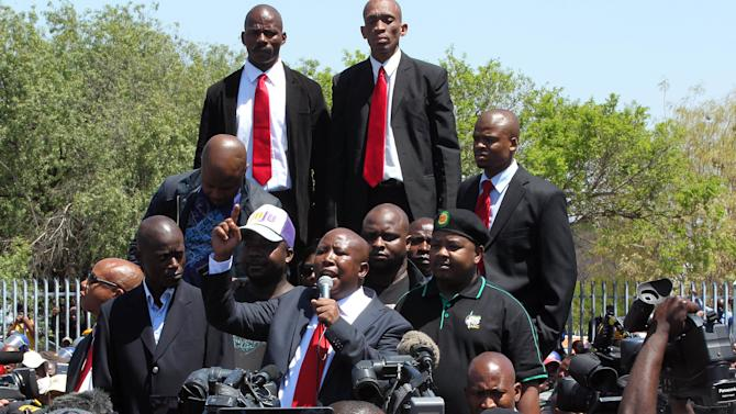 Firebrand politician Julius Malema, center, addresses his supporters after appearing at the Magistrate's Court in Polokwane, South Africa, Wednesday, Sept.  26, 2012, on charges of money laundering in connection with an improper government tender awarded to a company his family trust partly owns. (AP Photo/Themba Hadebe)