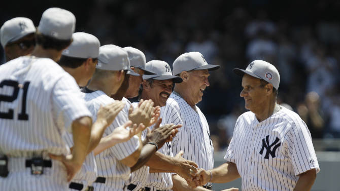 Former New York Yankees players, including Ron Guidry, third from right, and former Yankees pitching coach Mel Stottlemyre greet former New York Yankees manager Joe Torre, right, during introductions before the Yankees Old Timers Day baseball game at Yankee Stadium in New York, Sunday, July 1, 2012.  (AP Photo/Kathy Willens)
