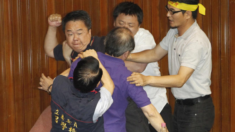 Ruling and opposition lawmakers fight on the legislature floor in Taipei, Taiwan, Friday, Aug. 2, 2013. Taiwanese lawmakers exchanged punches and threw water at each other Friday ahead of an expected vote that would authorize a referendum on whether to finish a fourth nuclear power plant on this densely populated island of 23 million people. (AP Photo/Wally Santana)