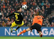 Yaroslav Rakitskiy (R) of Shakhtar Donetsk fights for the ball with Robert Lewandowski of Borussia Dortmund during their UEFA Champions League round 16 first leg match in Donetsk, on February 13, 2013. The match ended in a 2-2 draw