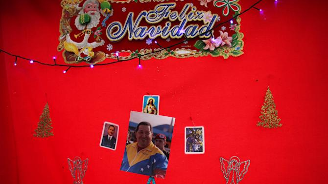 "A snapshot of Venezuela's President Hugo Chavez is surrounded by a trio of religious prayer cards and a sign that reads in Spanish; ""Merry Christmas"" on a red background hanging at a state-run market in Caracas, Venezuela, Friday, Dec. 28, 2012. The obsessive, circular conversations about Chavez's health dominate family dinners, plaza chit-chats and social media sites in this country on edge since its larger-than-life leader went to Cuba for emergency cancer surgery more than two weeks ago. The man whose booming voice once dominated the airwaves for hours at a time has not been seen or heard from since. (AP Photo/Fernando Llano)"