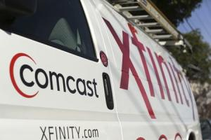 File photo of a Comcast sign is shown on the side of a vehicle in San Francisco